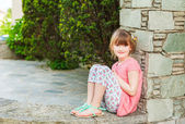 Outdoor portrait of a cute little girl on a nice sunny day, wearing coral dress and printed leggings — Zdjęcie stockowe