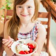 Cute little girl eating strawberry with ice cream on a balcony on a nice sunny day — Stock Photo #59714435