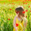 Summer portrait of a cute little girl playing in a poppy field on sunset, wearing yellow dress — Stock Photo #59715595