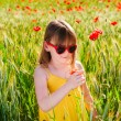 Summer portrait of a cute little girl playing in a poppy field on sunset, wearing yellow dress — Stock Photo #59718229