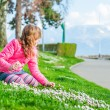 Beautiful little girl playing with flowers in a park on a nice sunny day in a early spring, wearing bright pink jacket — Stock Photo #59719207