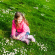 Beautiful little girl playing with flowers in a park on a nice sunny day in a early spring, wearing bright pink jacket — Stock Photo #59719249