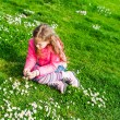 Beautiful little girl playing with flowers in a park on a nice sunny day in a early spring, wearing bright pink jacket — Stock Photo #59719267