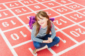 Close up portrait of a cute little girl with backpack in a schoolyard — Stock Photo