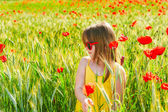 Summer portrait of a cute little girl playing in a poppy field on sunset, wearing yellow dress — Stock Photo