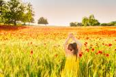 Summer portrait of a cute little girl playing in a pooppy field on sunset, wearing yellow dress — Stock Photo