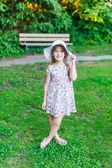 Adorable little girl in a white dress with flowers and hat in a park on a nice day — Stock Photo