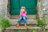 Outdoor portrait of a cute little girl, sitting on steps, weraing jeans and pink top — Stock Photo