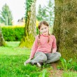 Adorable little girl sitting under the tree on a nice sunny day — Stock Photo #59796323