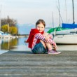 Cute little girl resting on a pier on a nice sunny day — Stock Photo #59797135