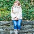 Outdoor portrait of a cute little girl sitting on a wall, wearing white warm jacket, jeans and boots — Stock Photo #59797317
