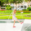 Cute little girl playing with a fountain on a nice summer day — Stock Photo #59797355