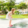 Cute little girl playing with a fountain on a nice summer day — Stock Photo #59797775