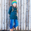 Winter portrait of a cute little girl, standing next to wooden wall, wearing, green cardigan, jeans, brown boots and colorful hat — Stock Photo #59798503