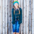 Winter portrait of a cute little girl, standing next to wooden wall, wearing, green cardigan, jeans, brown boots and colorful hat — Stock Photo #59798591