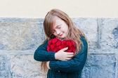 Cute little girl hagging big red heart with eyes closed — Stock Photo