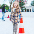 Cute little girl learning to skate with the support on a nice winter day — Stock Photo #64924617