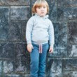 Outdoor portrait of a cute little boy against stone wall — Stock Photo #64926415