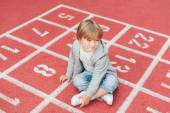 Adorable little boy resting on a schoolyard — Stock Photo