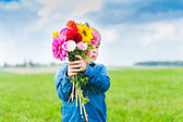 Beautiful bouquet of bright and colorful flowers holding by cute toddler boy — Stock Photo