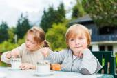 Adorable children drinking hot chocolate outdoors, spending good time on vacation in alpine mountains — Stock Photo