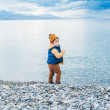 Cute toddler boy playing next to lake on a cold day — Stock Photo #64931791