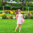 Outdoor portrait of a cute little girl in a park on a nice summer day — Stock Photo #64933397