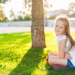 Adorable little girl resting under the tree in the park on a beautiful evening — Stock Photo #64941969