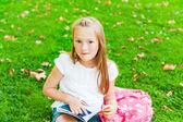 Cute little girl reading a book in a park after school — Zdjęcie stockowe