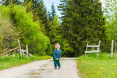 Cute toddler boy standing in the middle of the forest road and screaming — Stock Photo