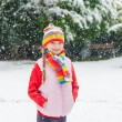 Winter portrait of a cute little girl under the snowfall, wearing red pullover, colorful hat and scarf — Stock Photo #65529701