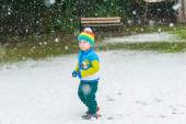 Winter portrait of a cute little boy under the snowfall, wearing christmas pullover and colorful hat — Stock Photo