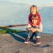 Two kids, little girl and boy resting by the lake on sunset, wearing pullovers and jeans, toned image — Stock Photo #66845409