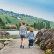 Two kids, brother and sister walking by the lake, wearing frocks and blue shoes, back view — Stock Photo #66845441