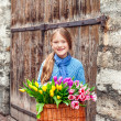 Outdoor portrait of a little girl with big bascket full of many fresh colorful tulips — Stock Photo #66845633