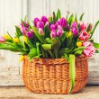 Big basket full of many fresh colorful tulips, outdoors — Stock Photo #66845665