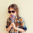 Portrait of a cute little girl of 7 years old, holding big colorful candy, wearing plaid shirt and black sunglasses — Stock Photo #66845717