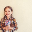 Portrait of a cute little girl of 7 years old, holding big colorful candy, wearing plaid shirt, toned image — Stock Photo #66845789