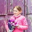Spring portrait of adorable little girl of 7 years old, wearing bright pink coat, holding beautiful bouquet of tulips — Stock Photo #66846123