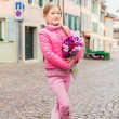 Spring portrait of adorable little girl of 7 years old, wearing bright pink coat, holding beautiful bouquet of tulips — Stock Photo #66846271