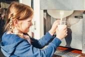 Küçük kız süt makineden bir çiftlikte alır — Stok fotoğraf