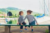 Two kids, little girl and boy resting by the lake, wearing frocks and blue shoes — Stock Photo