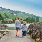 Two kids, brother and sister walking by the lake, wearing frocks and blue shoes, back view — Stock Photo