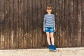 Outdoor portrait of a cute little girl, wearing frock, denim skirt and beautiful blue sneakers, standing against brown wooden wall — Stock Photo