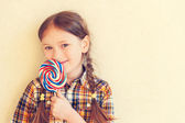 Portrait of a cute little girl of 7 years old, holding big colorful candy, wearing plaid shirt, toned image — Stock Photo