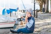 Прелестный маленький мальчик, едят мороженое на улице в холодную погоду — Стоковое фото
