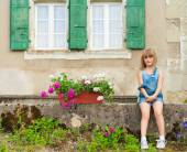 Summer portrait of a cute little girl of seven years old sitting in the yard — Stockfoto