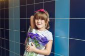 Portrait of a cute little girl with bouquet of aster autumn flowers — Stock Photo