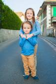 Two adorable kids in a city, girl and her little brother, wearing blue and beige clothes and moccasins — Stock Photo