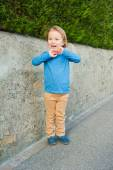 Outdoor portrait of adorable little boy wearing blue t-shirt, beige trousers and dark blue moccasins — Stock Photo